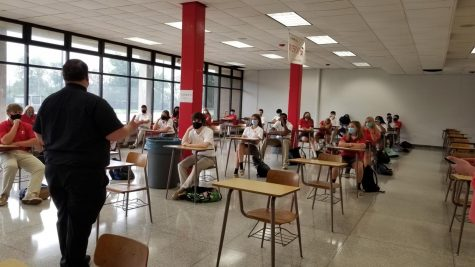 Fr. Mark Cavara speaks to students in the cafeteria, where desks have replaced tables so social distancing can be enforced.